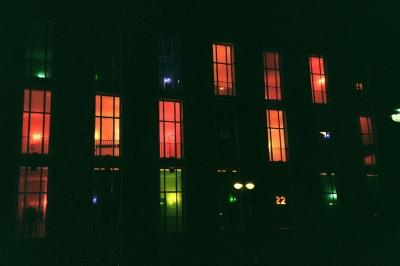 Haus im Dunkeln mit verschieden beleuchteten Fenstern