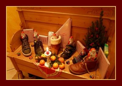 Stiefel und Schuhe auf einer Bank mit Nikoläusen
