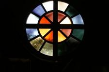 Rundes Fenster mit Farbsegmenten und Kreuz