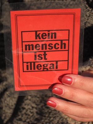 Frauenhand hält Zettel mit Aufschrift: Kein Mensch ist illegal