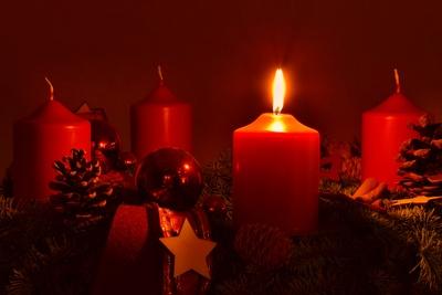 Adventskranz mit einer brennenden Kerze