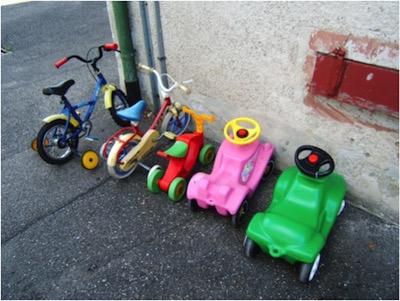 Parkende Kinderfahrraeder und Bobbycars