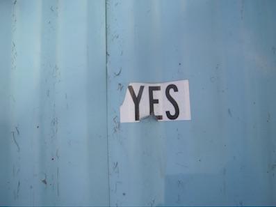 Türkise Wand mit einem weissen Zettel mit dem Wort YES