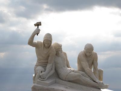 Steinskulptur Jesus wird ans Kreuz genagelt