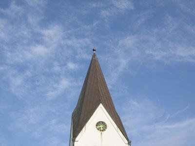 Kirchturm vor Sommerwolken