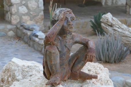 Sitzende Menschen-Statue auf einem Stein