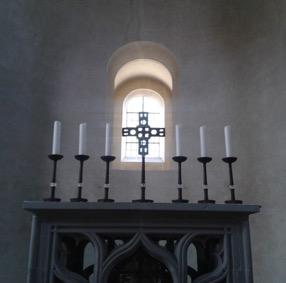Altar mit 6 Kerzen und Kreuz im Gegenlicht eines Kirchefnensters