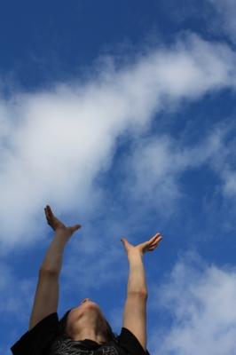 Hochgestreckte Arme zum blauen Himmel