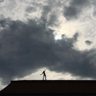 Balancierender Mensch auf dem Dach