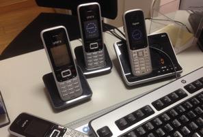 Vier Mobiltelefone neben einer Computertastatur