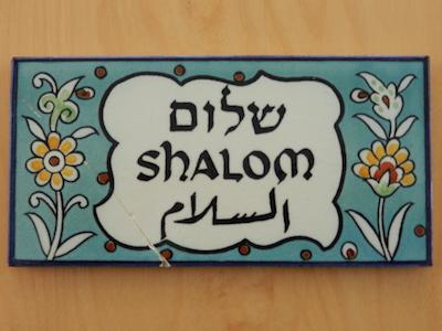 Wandfliese mit Blumen und dem hebräischen-lateinischen-arabischenSchriftzug Shalom-Salam