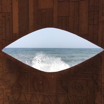 Metallwand mit Augenausschnitt und aufbrausendem Meer