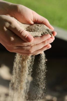 Hände aus denen Sand rieselt