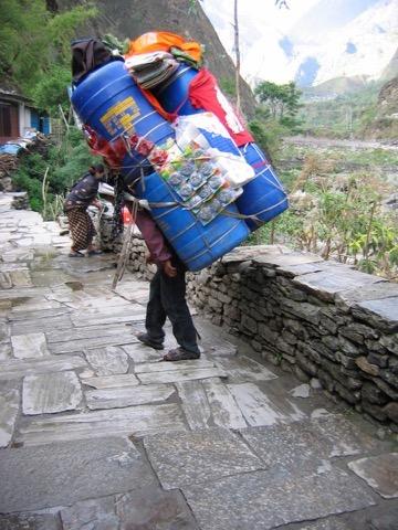 Mensch mit viel Gepäck auf dem Rücken