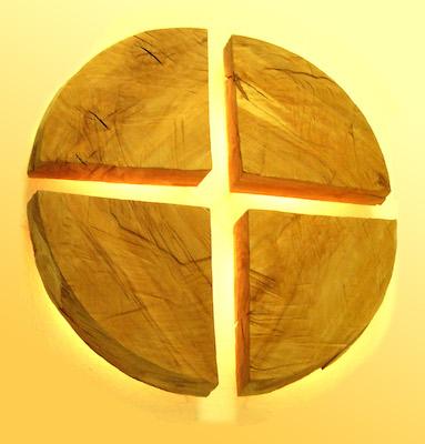 Kreuz aus vier Holz-Kreissegmenten im Gegenlicht