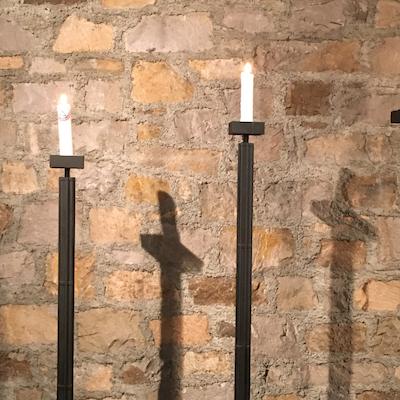 2 brennende Altarlkerzen mit Kreuz-Schatten