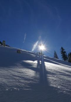 Gipfelkreuz im Gegenlicht und Schneelandschaft