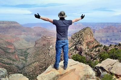 Mann mit geöffnetnen Armen auf einem Berg