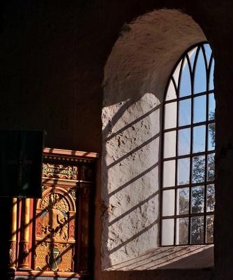 Sonnenstrahlen durch ein Kirchenfenster erleuchten den Raum und werfen Schatten der Fensterkreuze