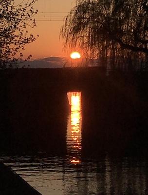 Sonnenuntergang an einer Eisenbahnbrücke mit Spiegelung im Wasser
