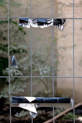 Abgerissenes Plakat am Zaun