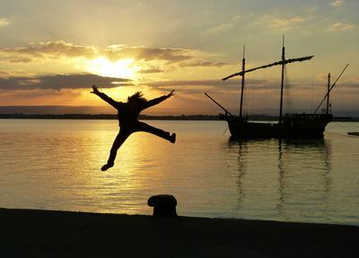 Freudenhochspringende Person im Sonnenuntergang an einer Kaimauer