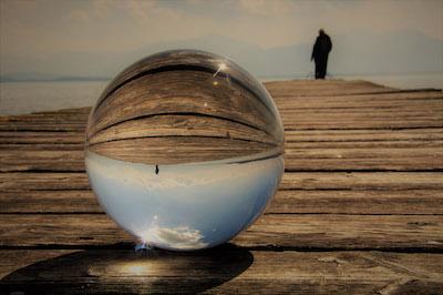 Person auf einem Steg, gespiegelt in einer Glaskugel