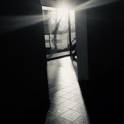 Licht bricht sich durch eine Glastür, schwarz-weiss