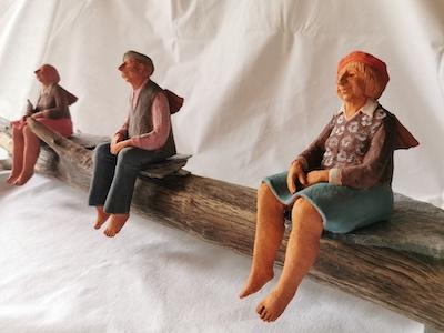 Auf ein Bank sitzen Menschenfiguren in Abstand zueinander