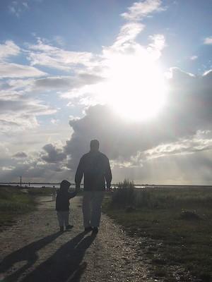 Elternteil mit Kind auf einem Weg im Gegenlicht