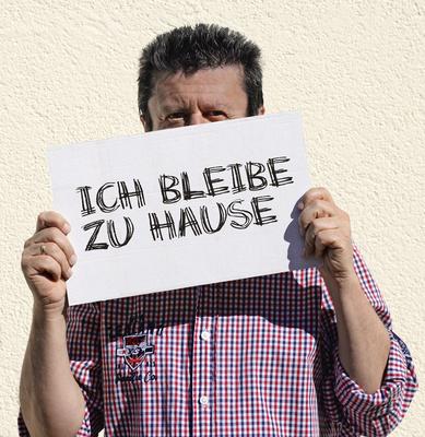 Mann mit Schild: ICH BLEIBE ZU HAUSE