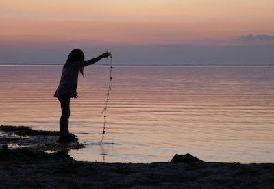 Mädchen am See bei Sonnenuntergang