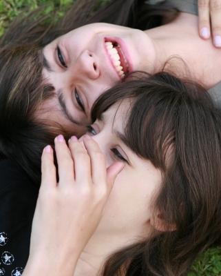 Zwei liegende Frauengesichter, eine hat eine Hand vor dem Mund