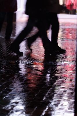 Beine, die abends auf nasser Pflasterstrasse unterwegs sind