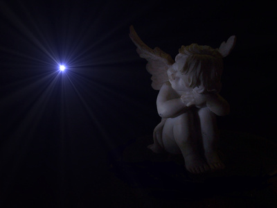 Engel im Dunkeln mit einem Licht
