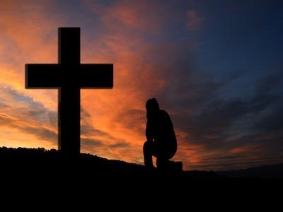 Gipfelkreuz mit anbetender Person