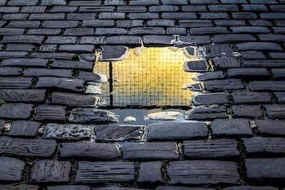 Gitter-Reflektionen zwischen schwarzen Pflastersteinen