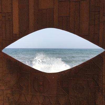 Meeresgischt durch augenförmigen Auschnitt einer Metallplatte