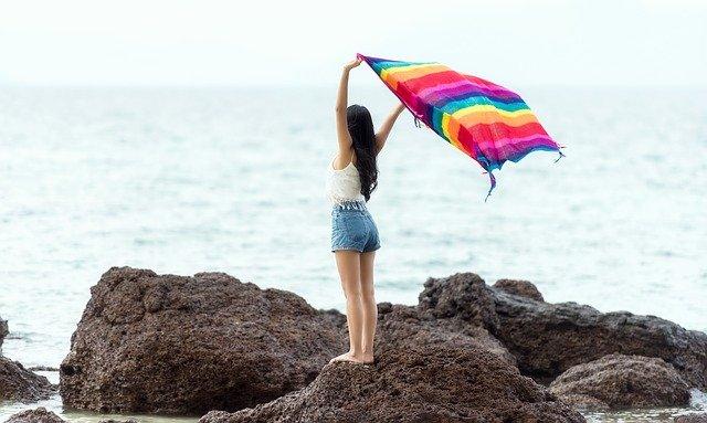 Frau mit Regenbogenfahne am Meer
