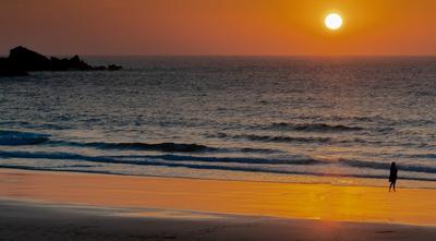 Frau am Meer beim Sonnenuntergang